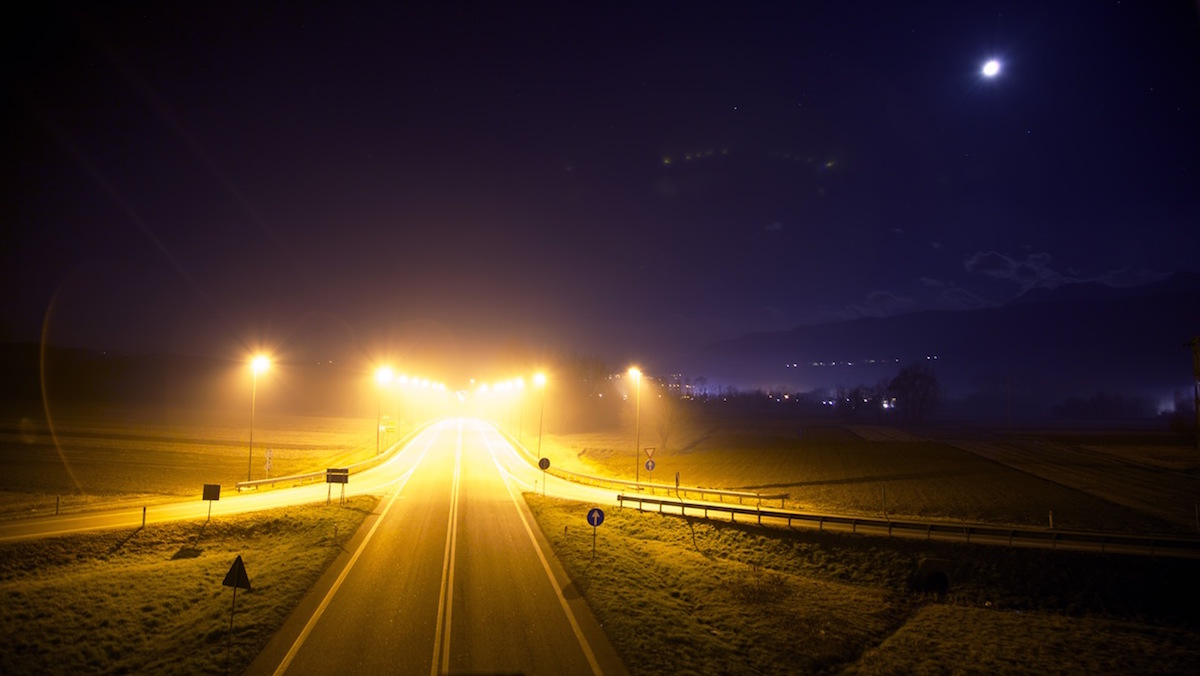 Picture of a road illuminated by street lights late at night